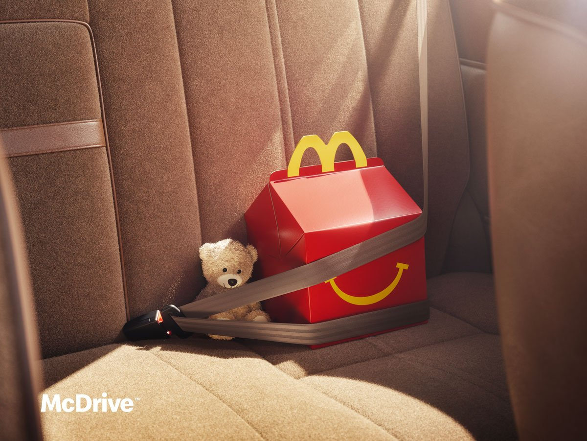 McDonald's happy meal sitting in a car seat next to a teddy bear and with its seatbelt on.