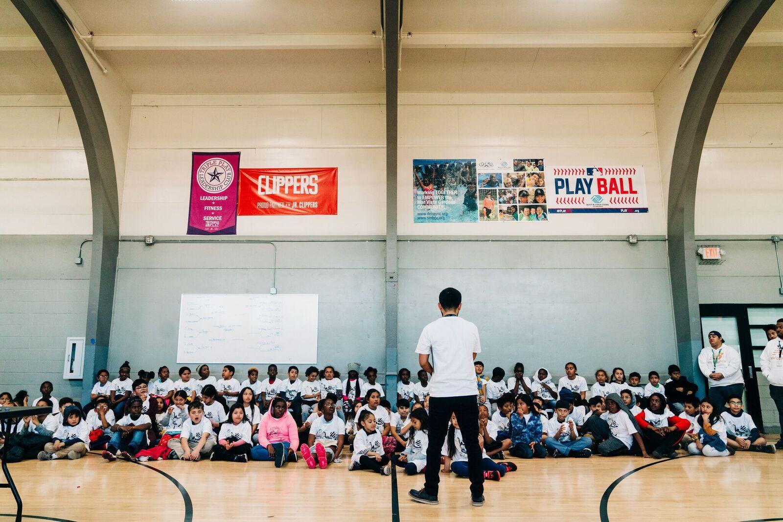 Instructor speaking to children in a gymnasium
