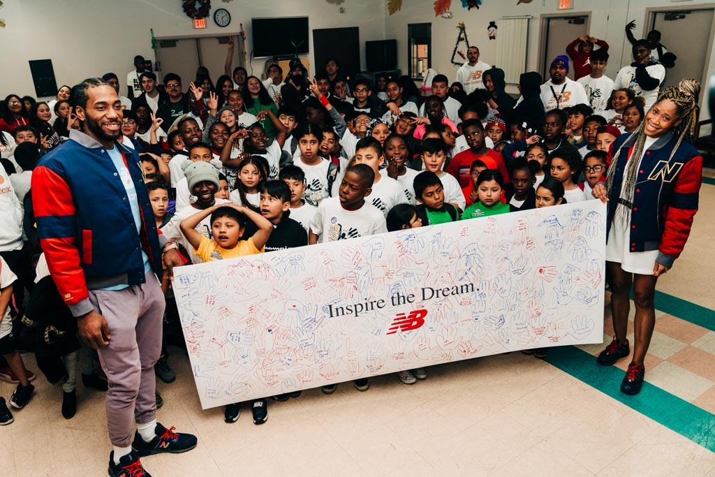 "Kawhi Leonard and Samia Akbar holding a banner that says ""Inspire the Dream"""