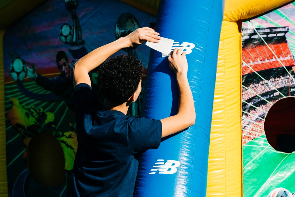 Child placing NB sticker onto inflatable structure