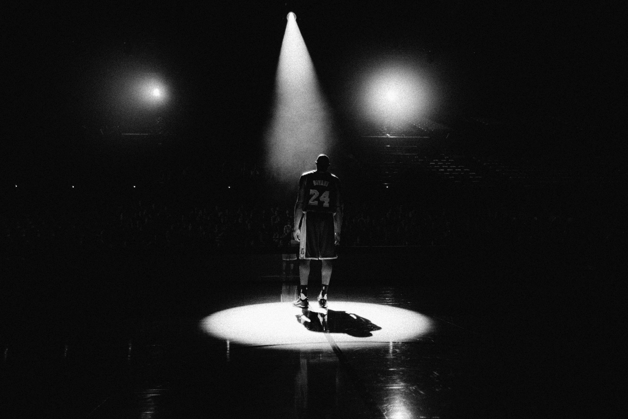 Kobe Bryant standing in the middle of a basketball court with a spotlight shining on him