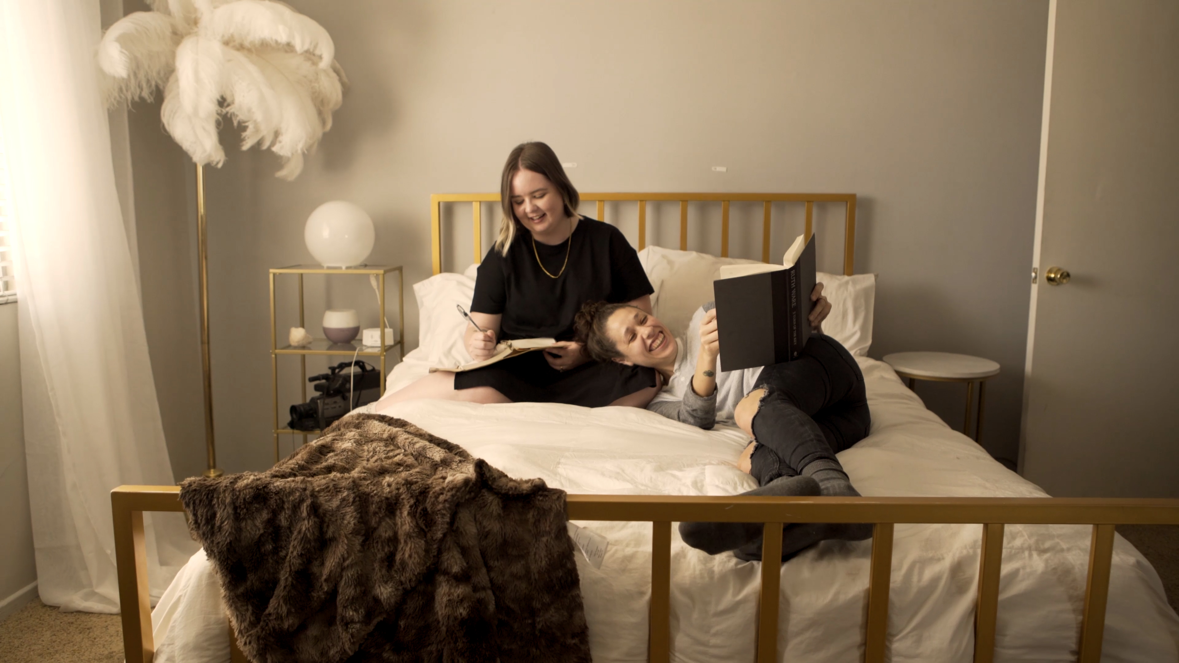 2 women sitting on a bed, laughing.
