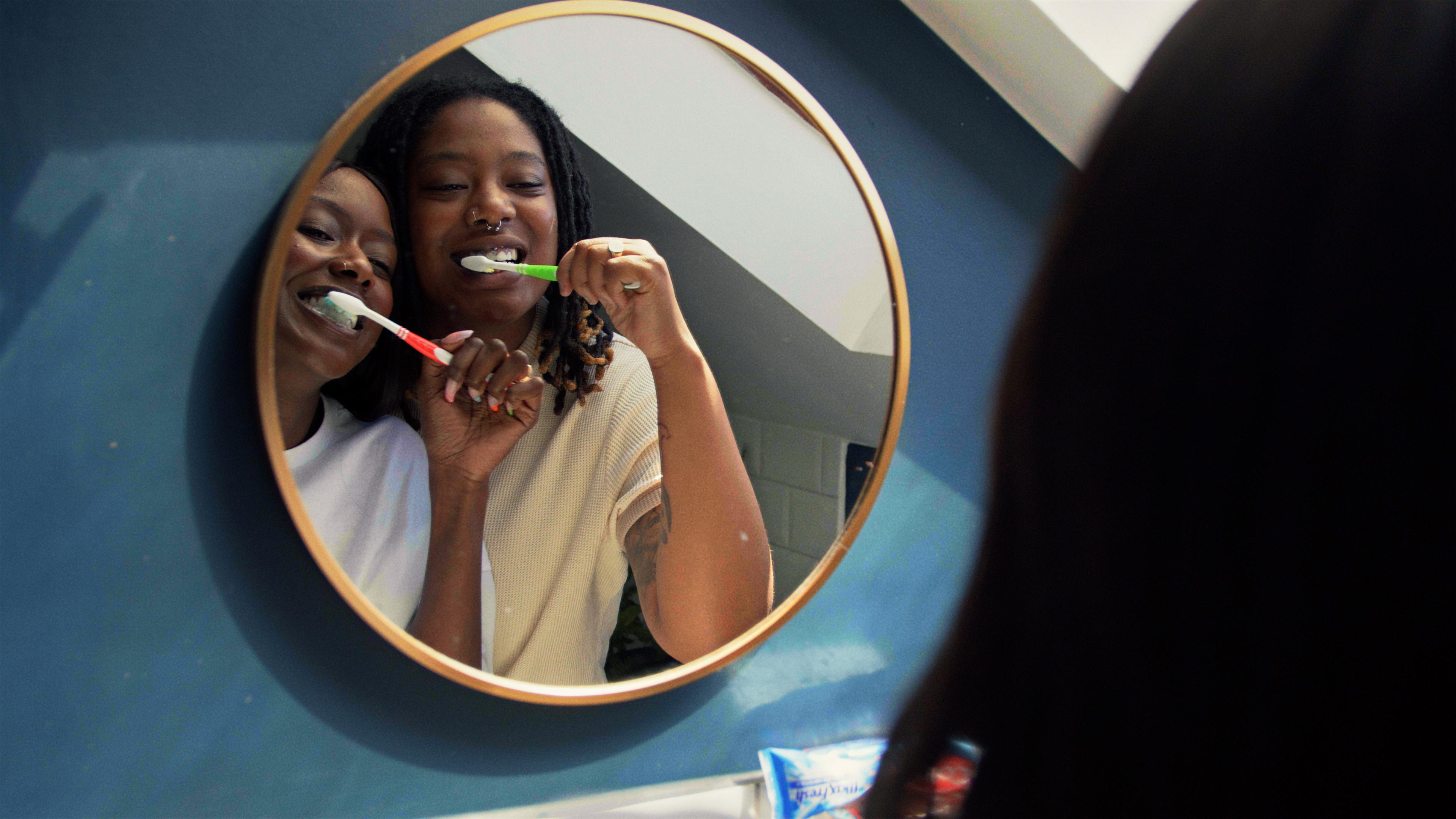 2 women brushing their teeth and smiling